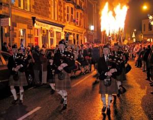 Tradičně oblečení dudáci za doprovodu pochodní o svátku Hogmanay ve skotském městečku Comrie.
