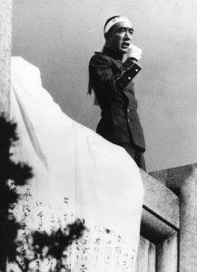 Mišima pronáší svůj projev k davu shromážděnému pod balkonem. Za chvíli bude mrtev.