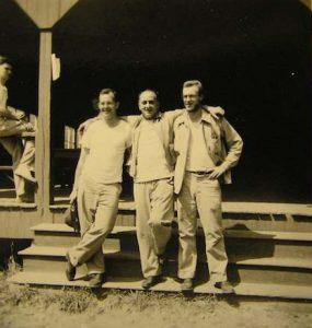 Muzafer Sherif (uprostřed) s pracovníky skautského tábora. Sociální psycholog tureckého původu Muzafer Sherif (1906 – 1988) získal magisterský titul na Harvard University a doktorát na Columbia University, nejprestižnějších amerických univerzitách.
