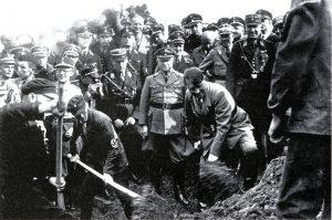 Fyzické práce se štítící Hitler pózuje s lopatou při zahájení výstavby dálnice spojující Heidelberg a Frankfurt.