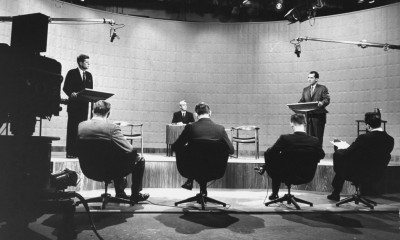 Presidential candidates Sen. John Kennedy & Repub. Rep. Richard Nixon (R) standing at lecterns as moderator Howard K. Smith (2R) presides at desk while 4 TV newsmen (backs to camera) ask questions during their debate of campaign issues in TV studio.  (Photo by Francis Miller/The LIFE Picture Collection/Getty Images)